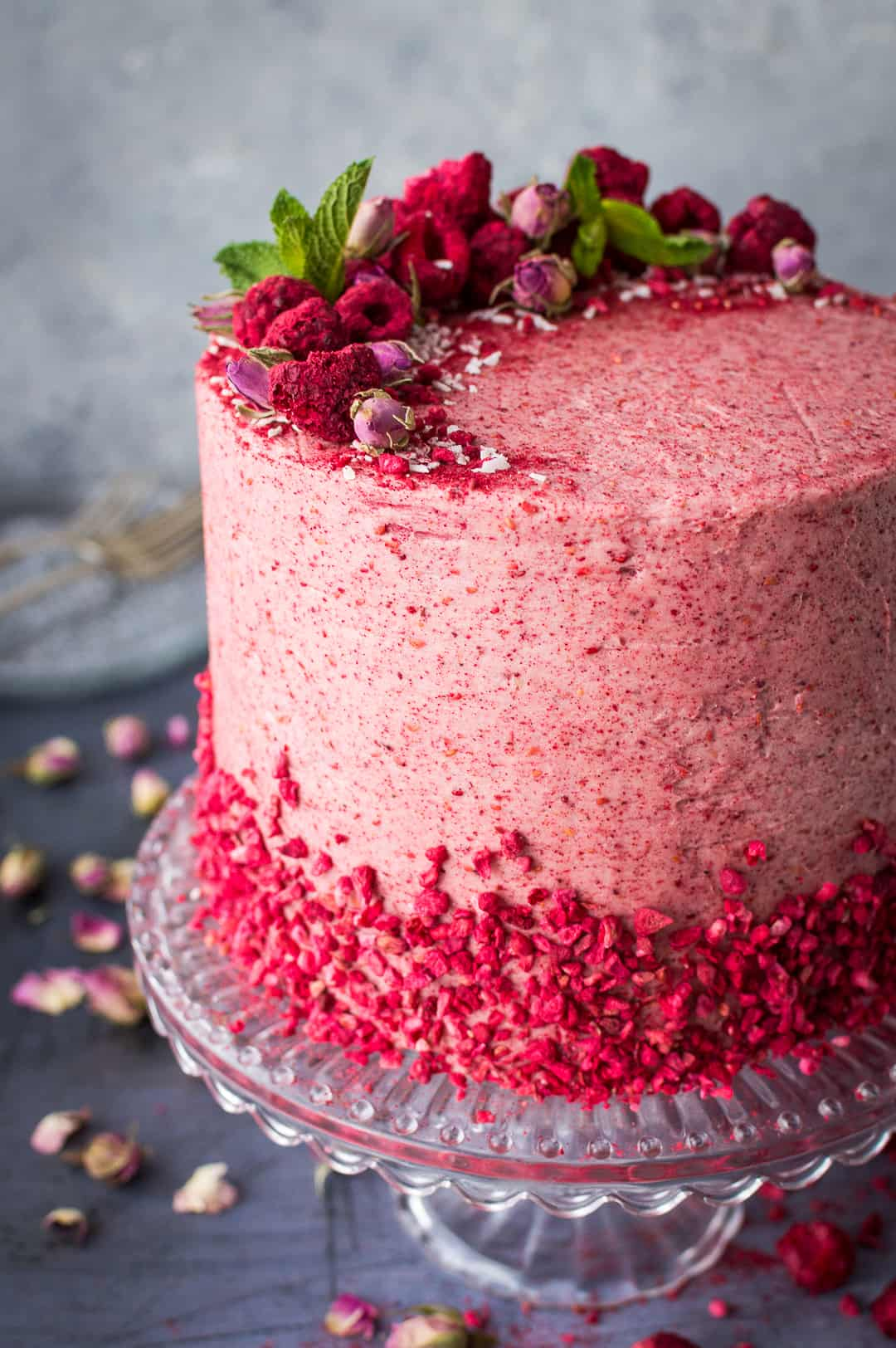 Side view of raspberry coconut lemon layer cake decorated with freeze dried raspberries.