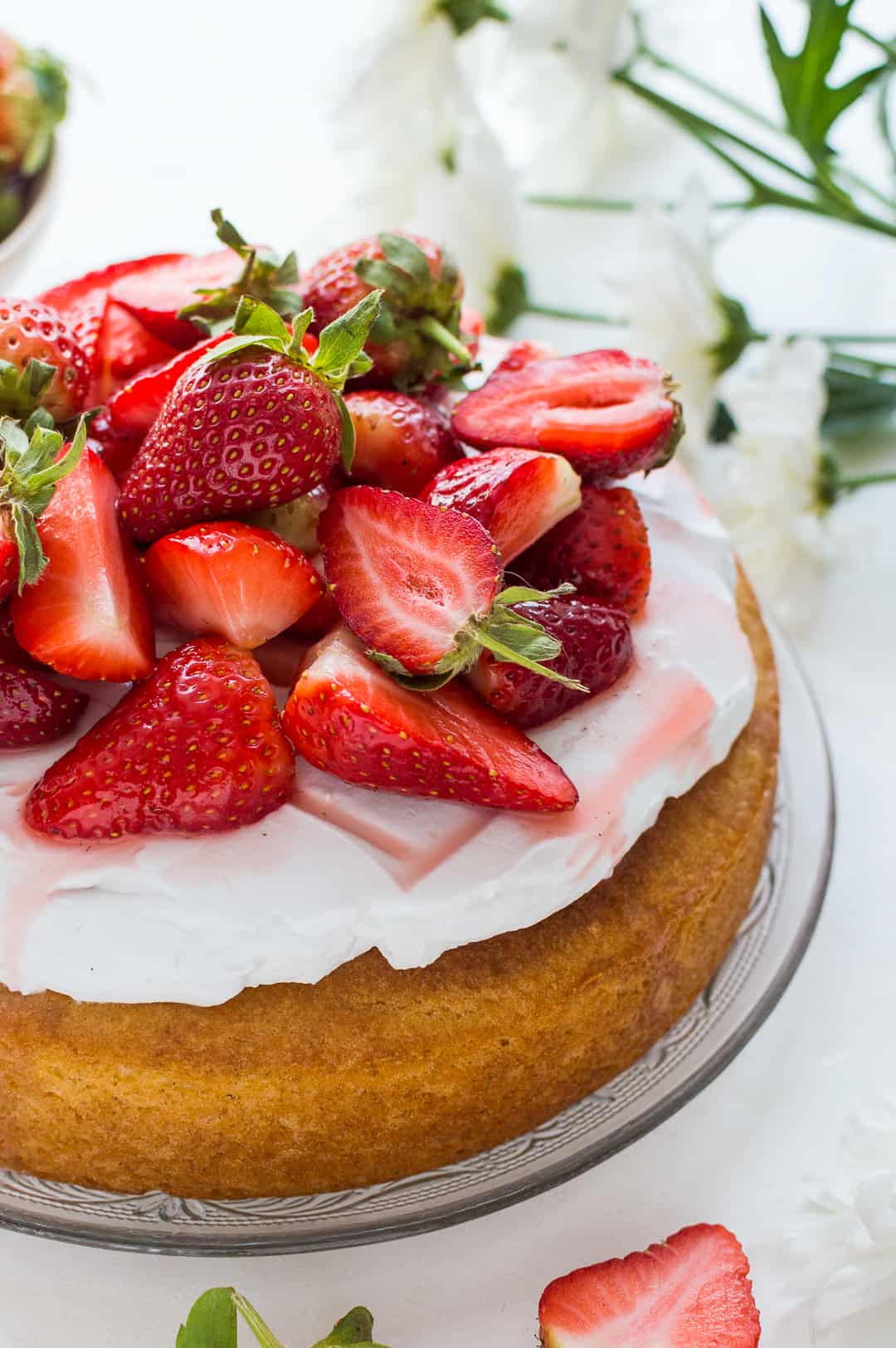 A close up shot of simple vegan lemon almond cake topped with coconut whipped cream and macerated strawberries on a white background.