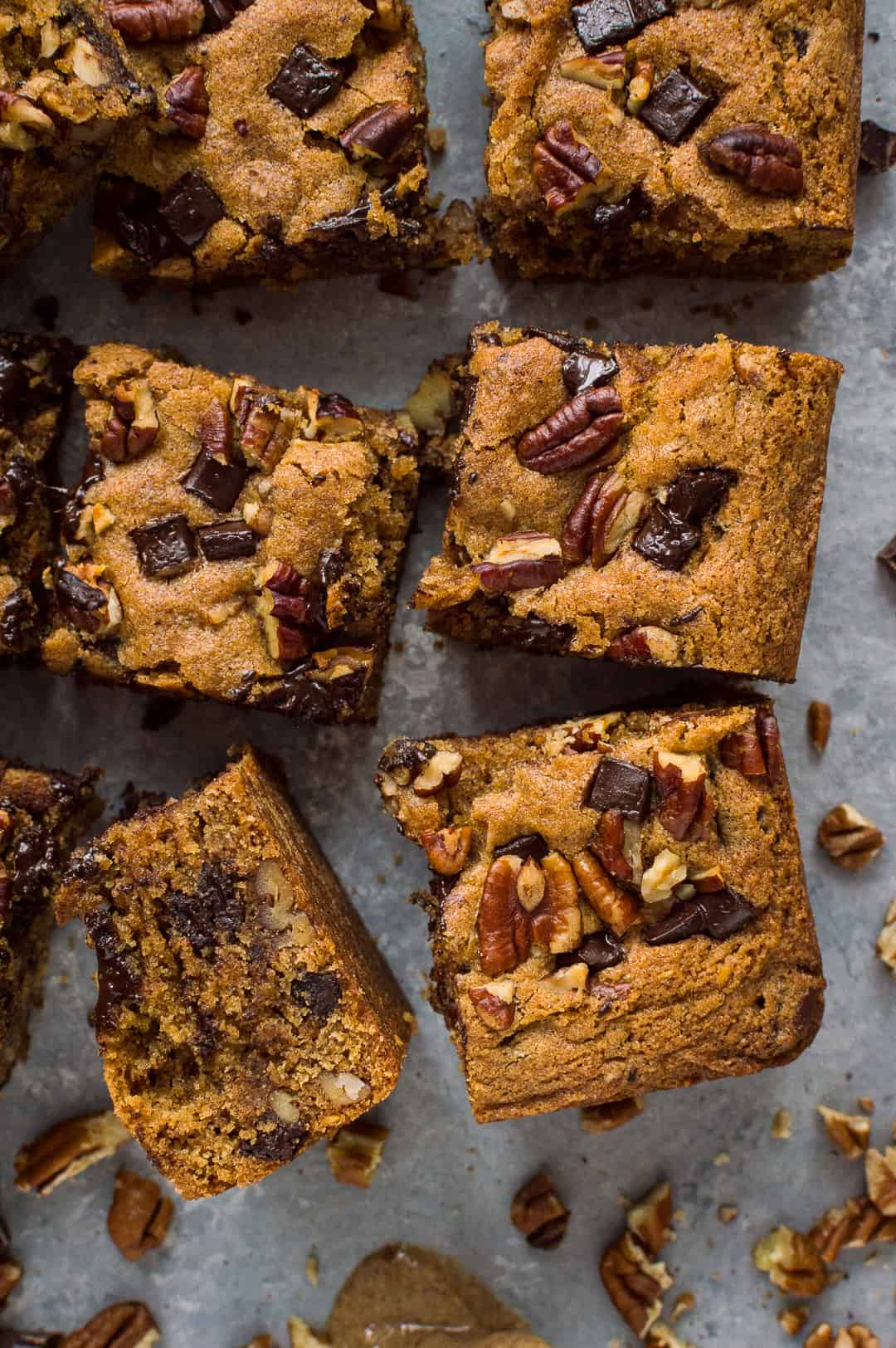 Squares of egg and dairy free peanut butter chocolate chip pecan bars.