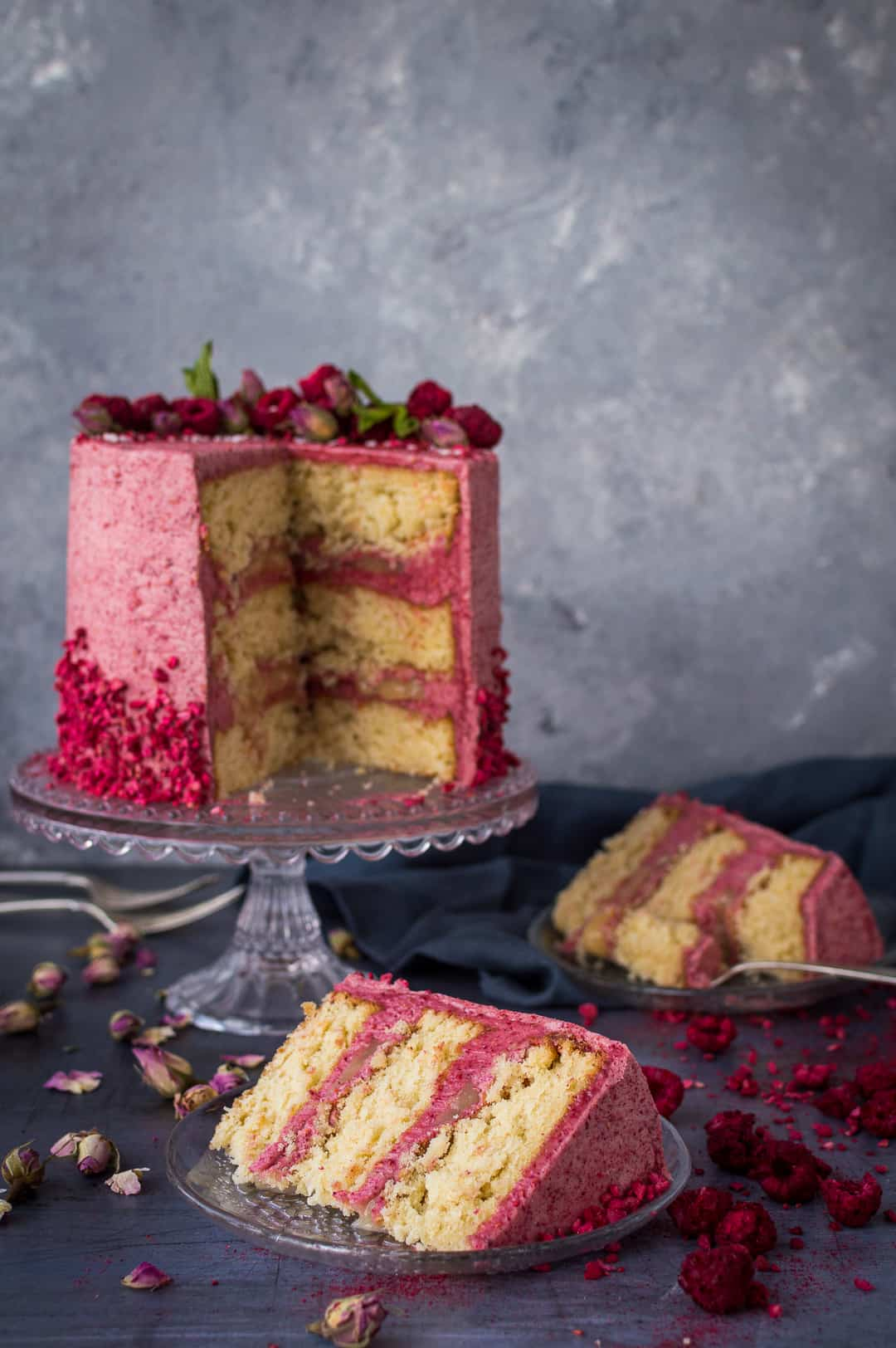 Sliced raspberry, coconut and lemon layer cake on a glass cake stand and grey background.