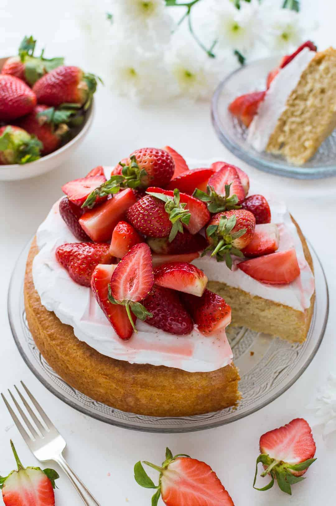 Vegan lemon almond cake with coconut whipped cream and macerated strawberries on a glass plate on a white background with strawberries, flowers and a slice of cake.