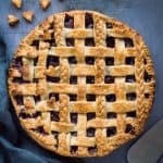 Unsliced baked vegan blueberry pie topped with a coconut oil pastry lattice and pastry braids and hearts.