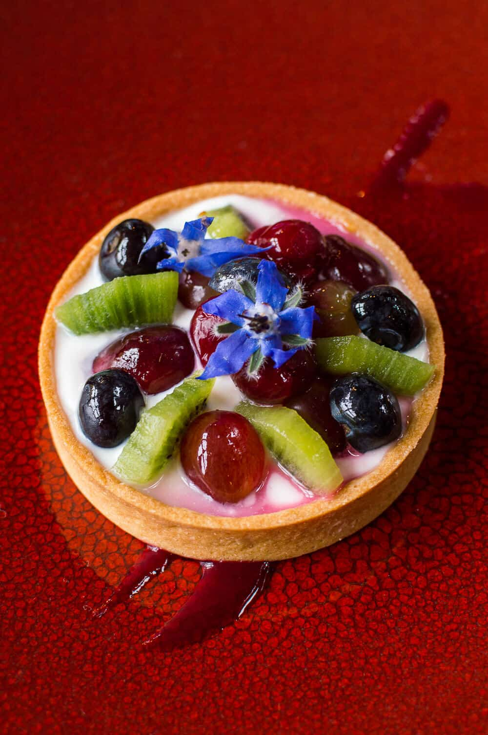 fruit tart with honey'd yogurt with edible flowers on a red plate