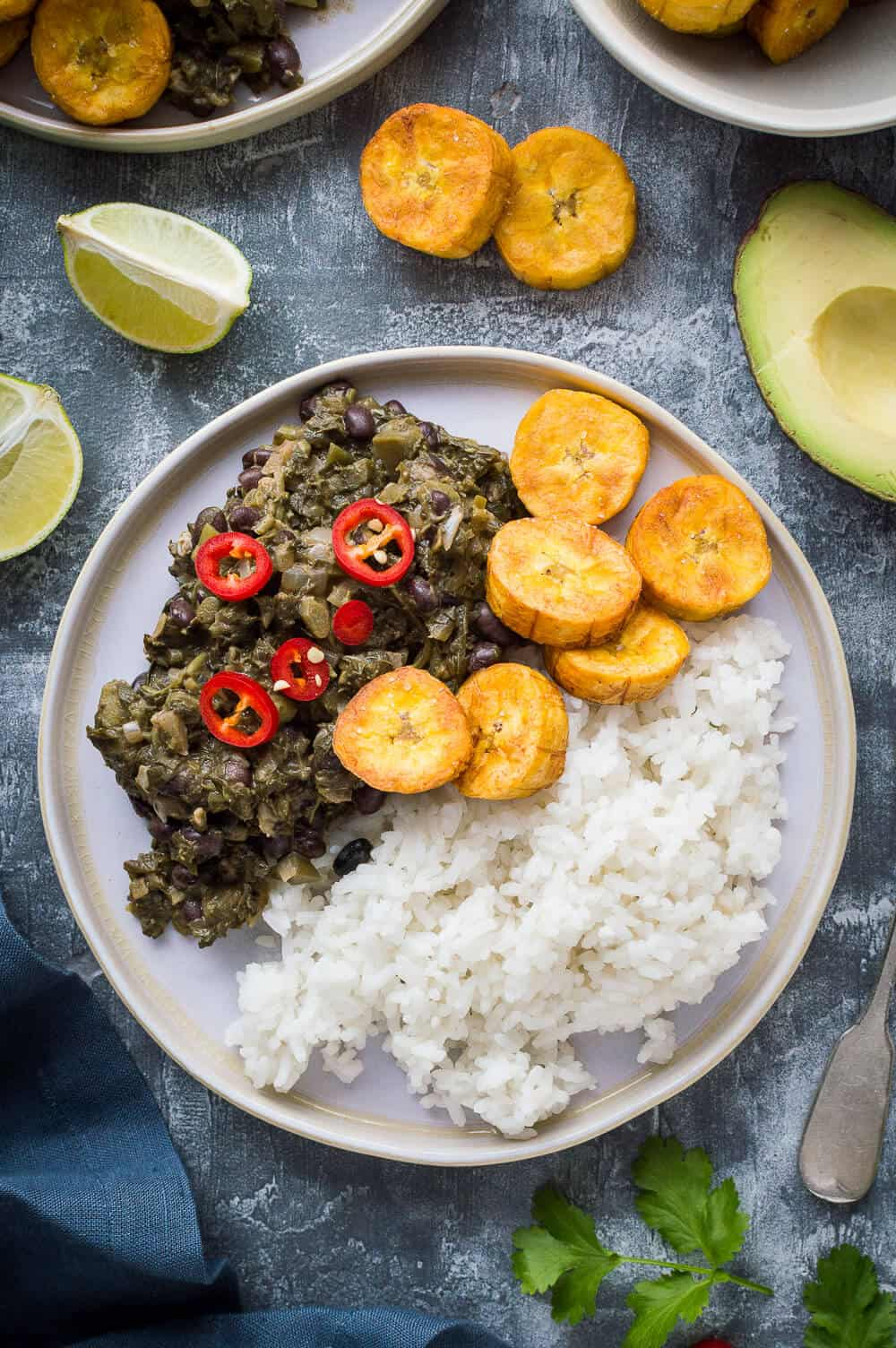 A plate of vegan spiced black beans and callaloo with coconut rice, fried plantain and red chilli.
