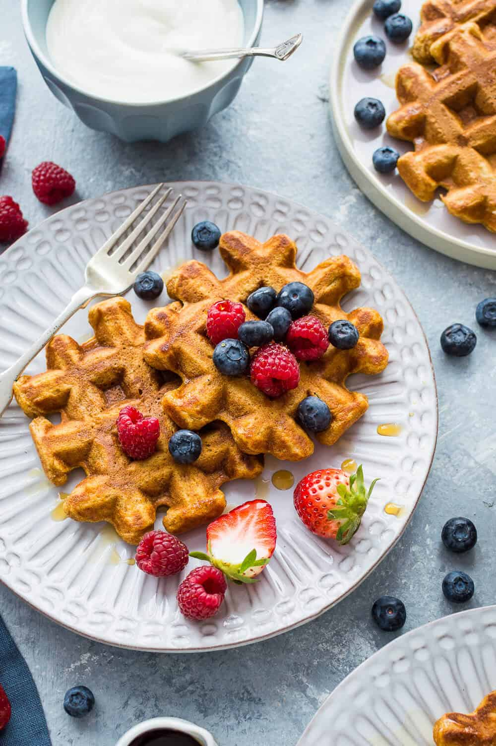 Healthier sweet potato waffles on a white plate with berries and maple syrup.