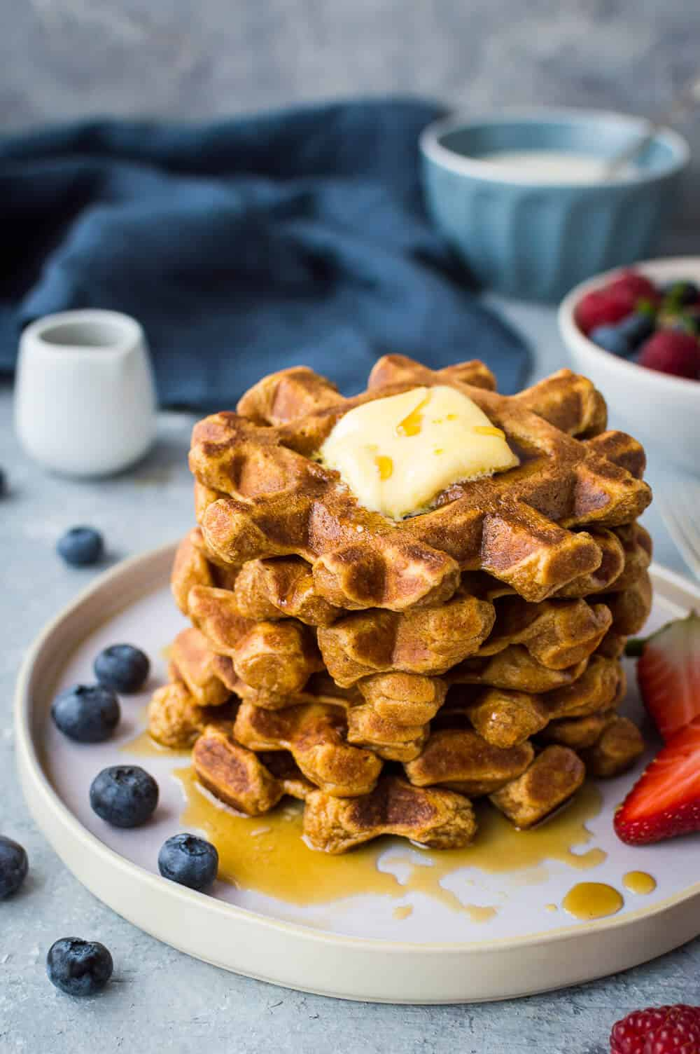 A stack of healthier sweet potato waffles with butter, maple syrup and berries.