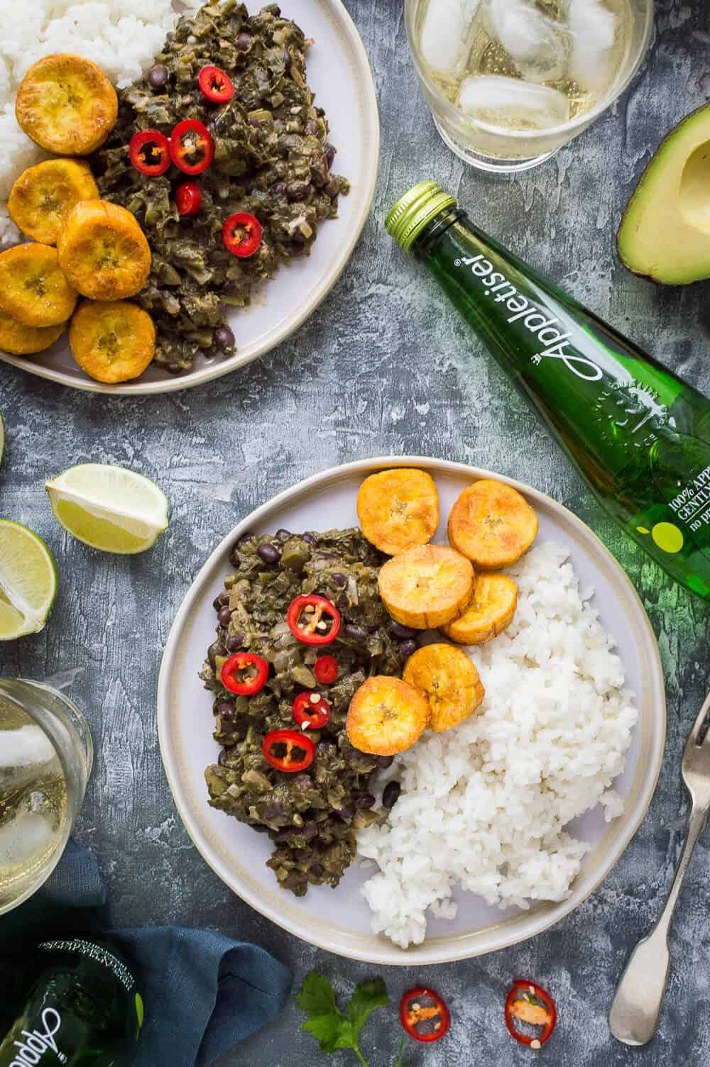 Two plates of vegan spiced black beans and callaloo with coconut rice and fried plantain on a grey background with lime, avocado and Appletiser.