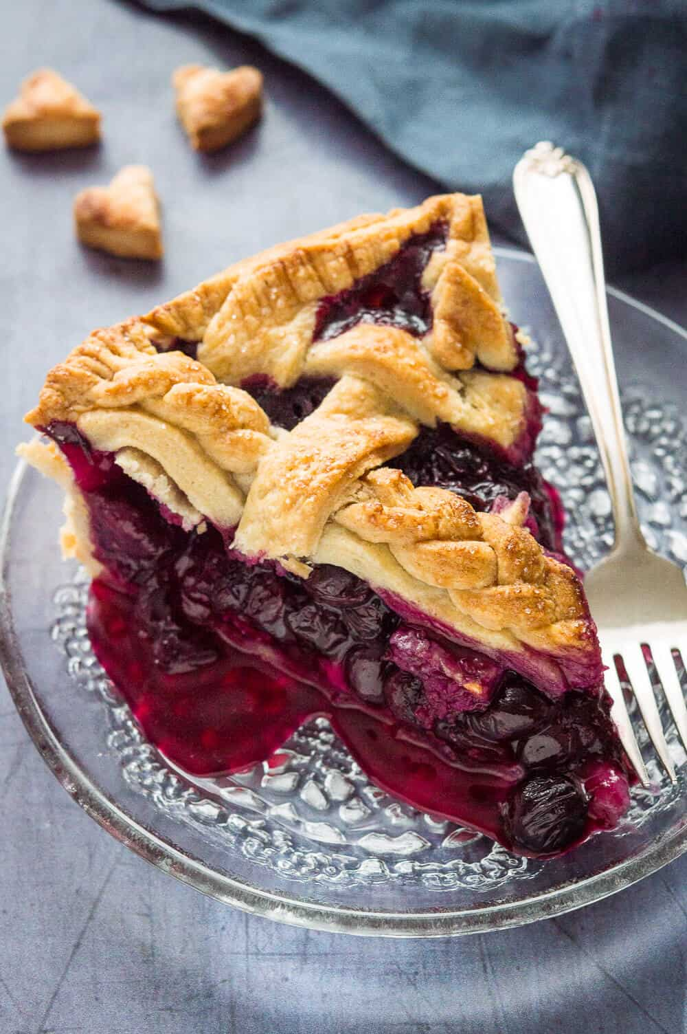A side shot of a slice of lattice topped blueberry pie made with vegan coconut oil pastry.