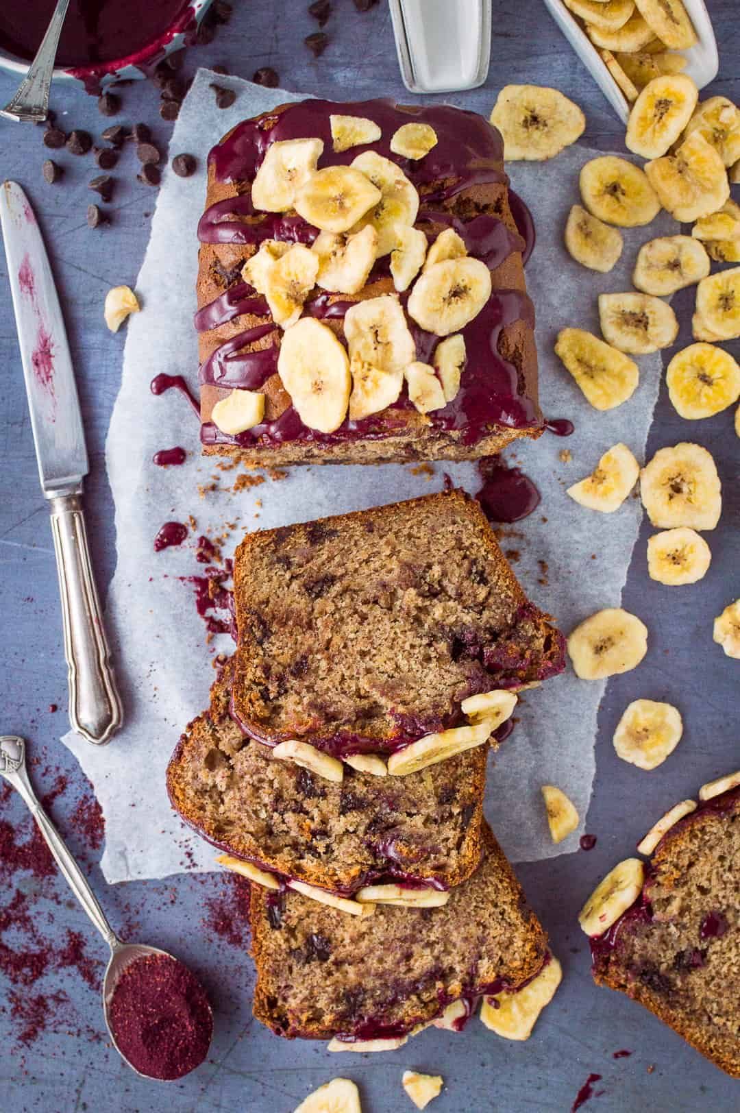 Vegan chocolate chip banana bread - a vegan version of everyone's favourite bake. Easy to make using storecupboard ingredients, packed with chocolate chips and topped with a blueberry glaze; this banana bread is seriously good!