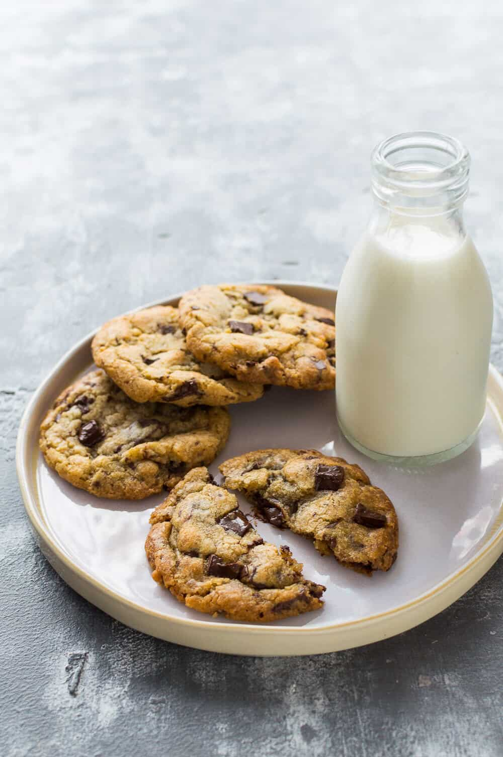 Photo of a white plate of vegan chocolate chip cookies with a glass bottle of almond milk on a grey background