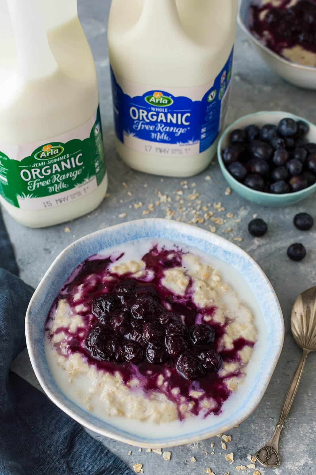 banana porridge with blueberry compote with two bottles of Arla organic milk