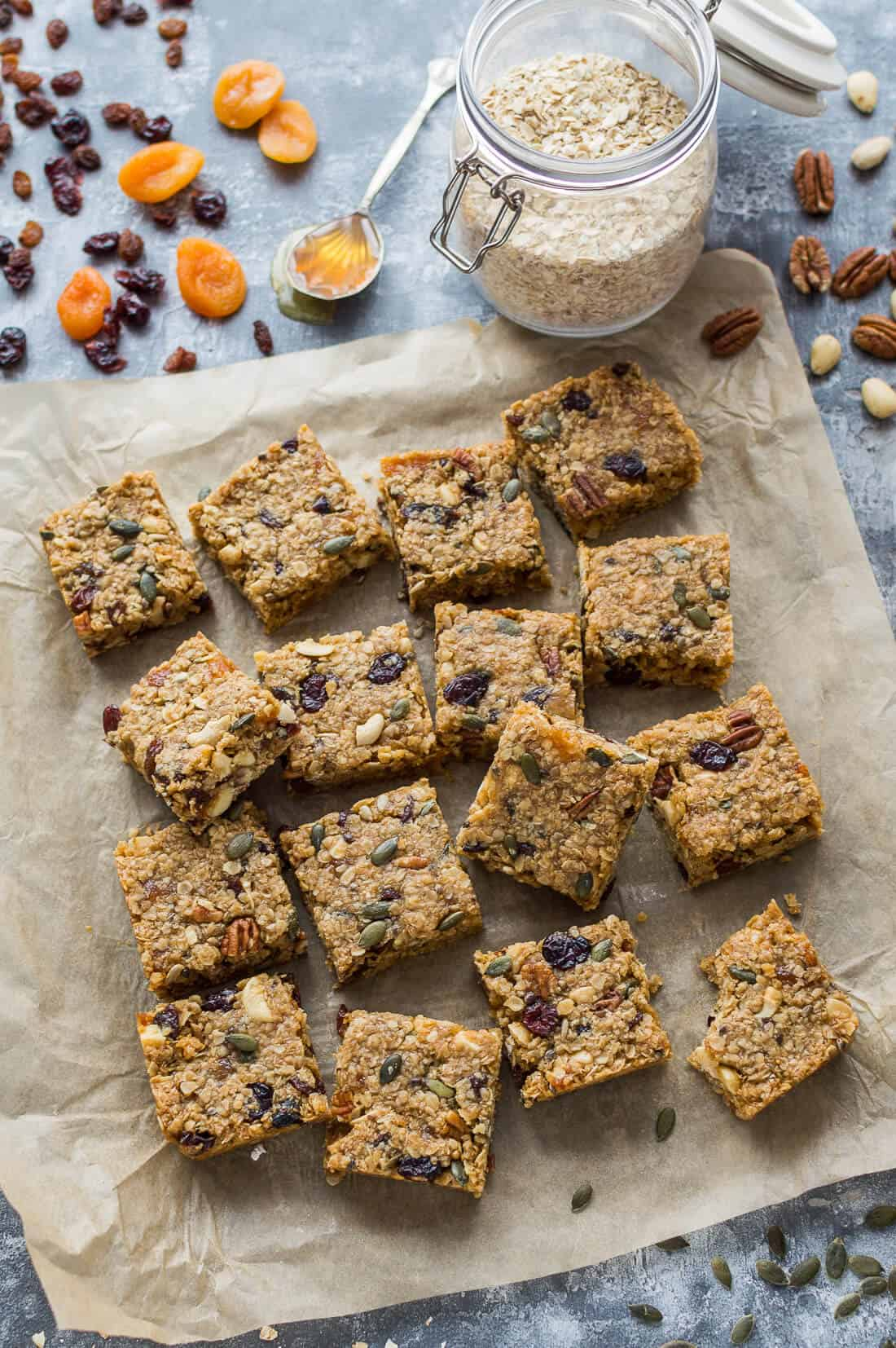 Squares of dairy free fruit and nut flapjacks (oat cookie bars) on baking parchment with a jar of oats and fruits, nuts and seeds