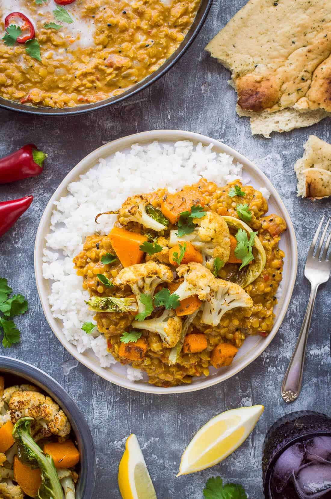 A plate of red lentil dhal and white rice with roasted cauliflower and butternut squash.