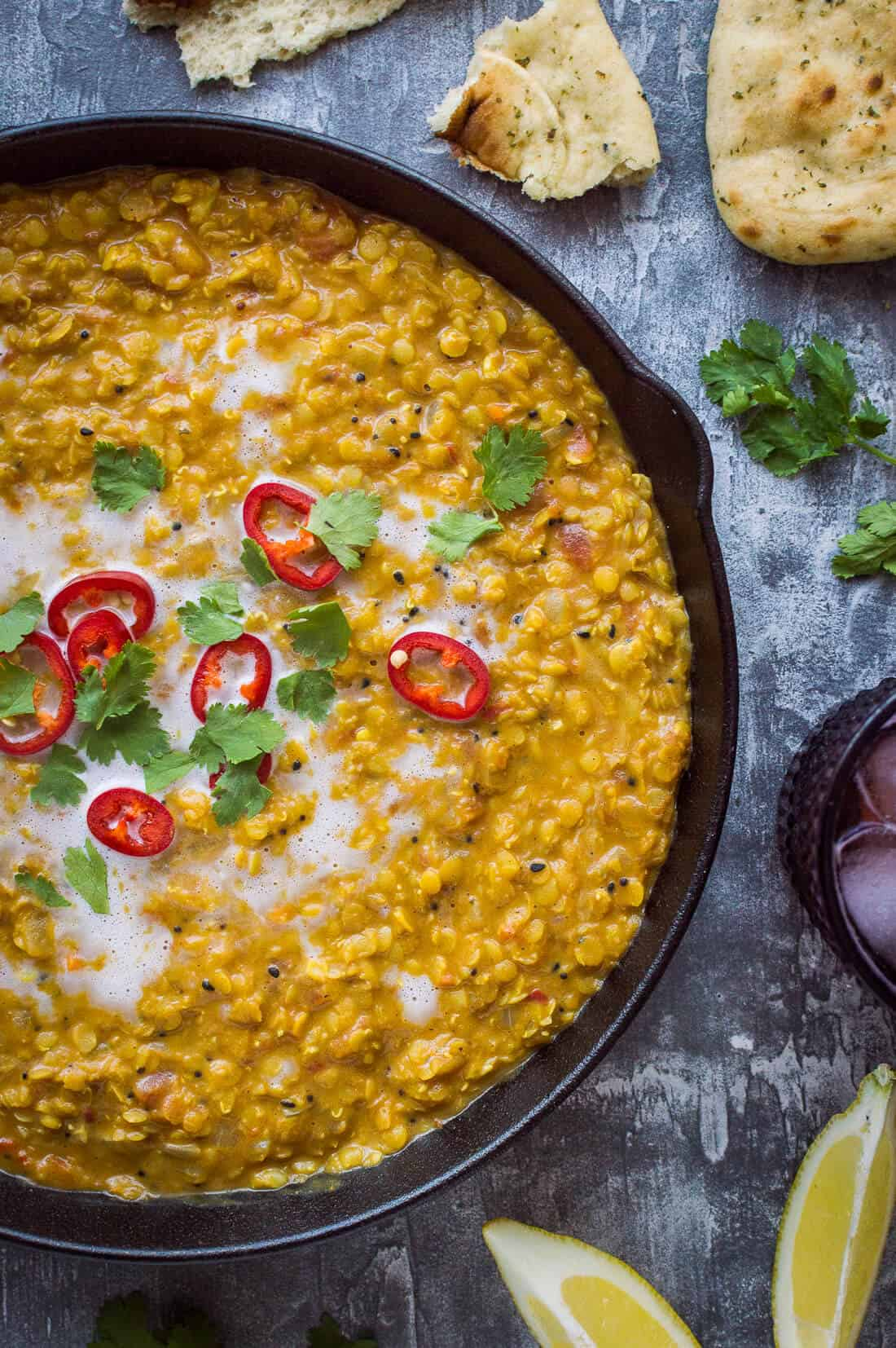 A close up of a pan of vegan red lentil dhal topped with red chilli, coriander and coconut milk