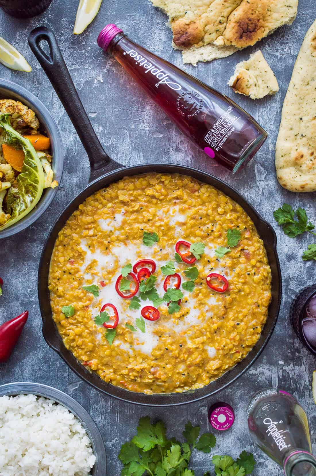 A pan of vegan red lentil dhal topped with red chilli, coriander and coconut milk with a bottle of Appletiser