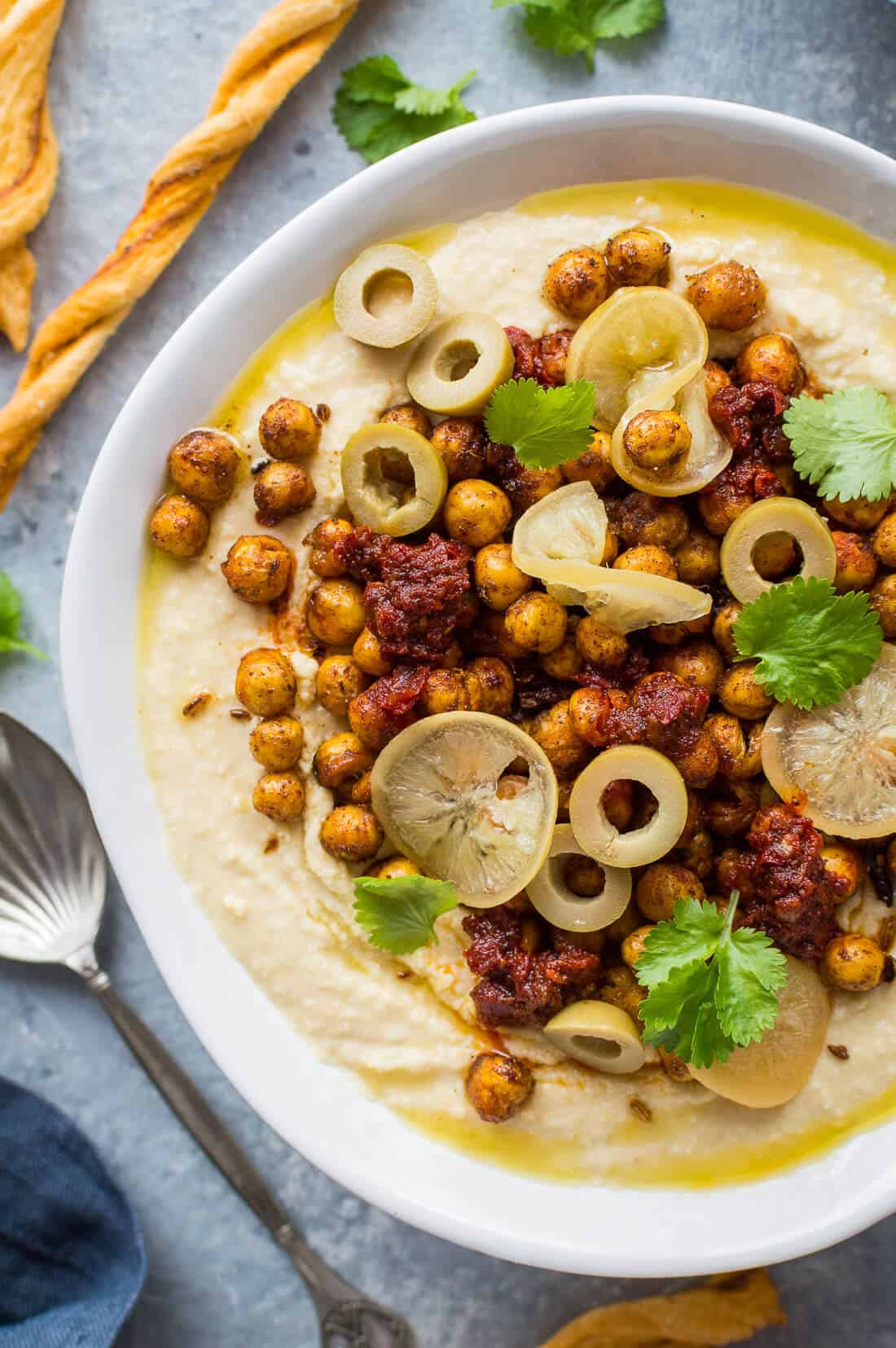 close up of loaded hummus bowl with spiced crispy roasted chickpeas, preserved lemon and olives