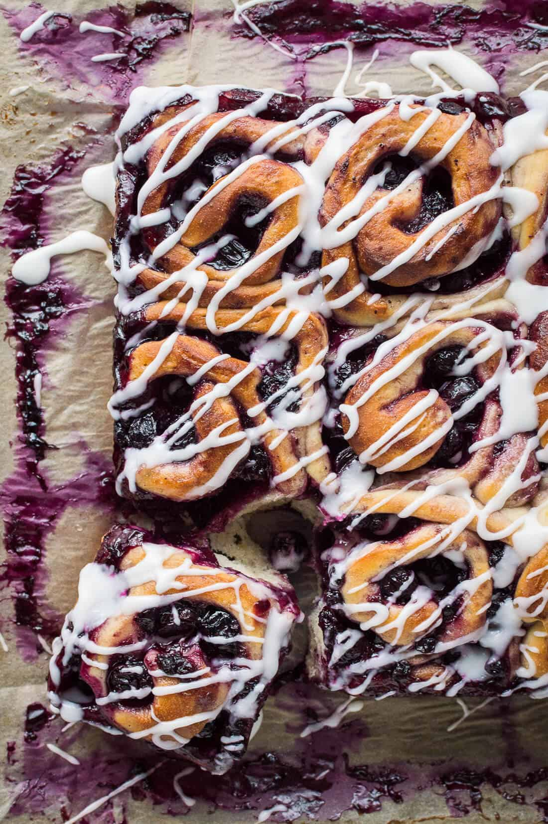 A top down shot of vegan lemon blueberry sweet rolls drizzled with lemon glaze on a sheet of baking parchment