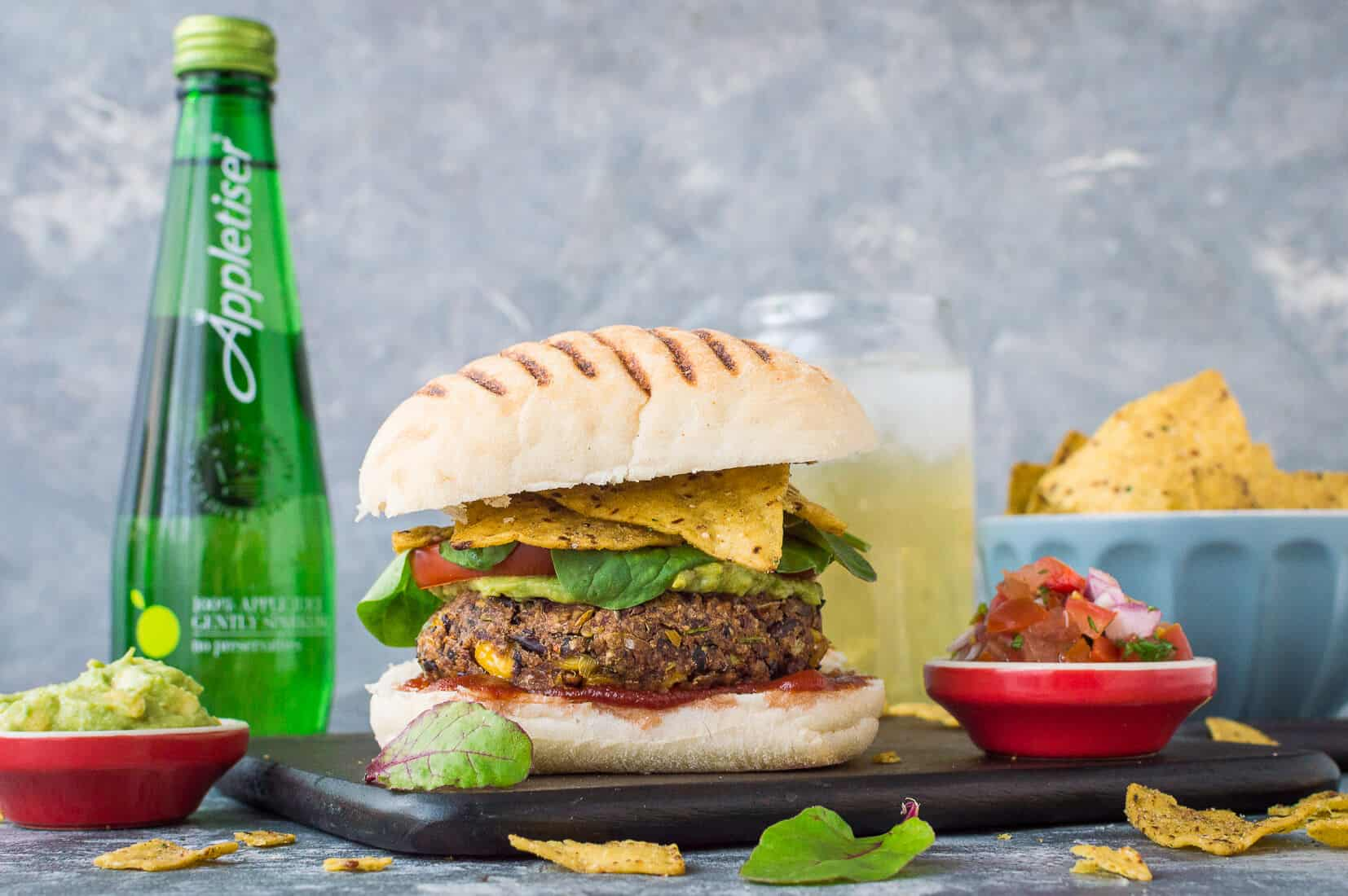 Vegan mexican bean burger in a bun on a wooden board with tortilla chips, salsa and Appletiser
