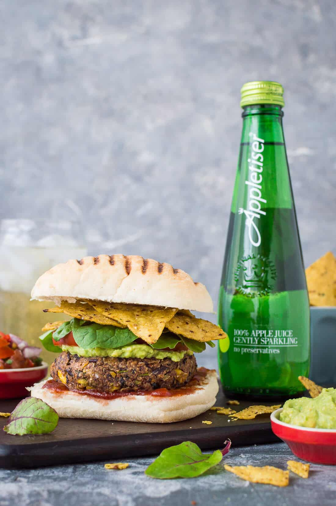 Vegetarian bean burger with tortilla chips, guacamole and salsa on a wooden board with a bottle of Appletiser
