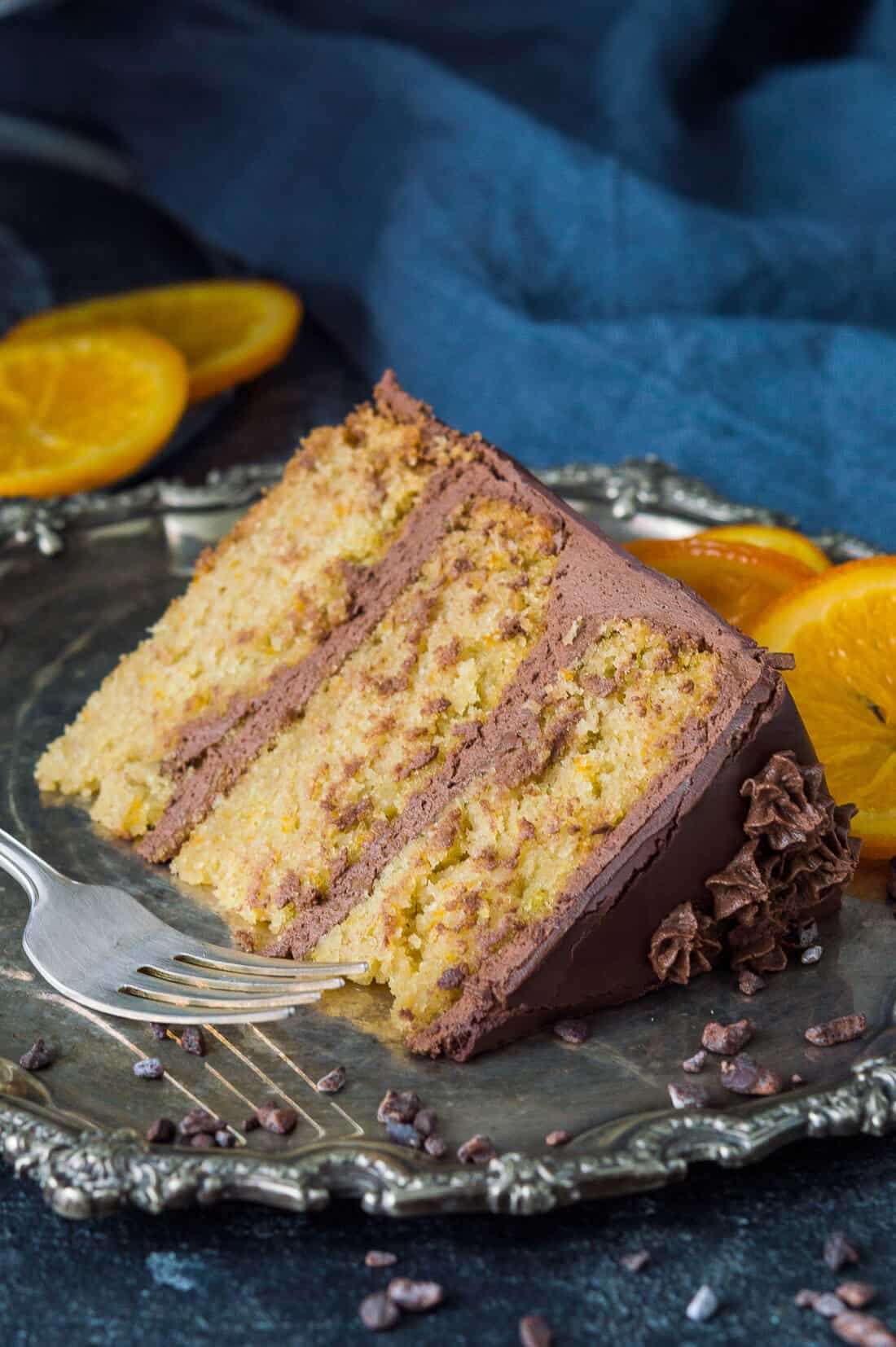 A slice of vegan orange and almond cake with vegan chocolate orange buttercream and candied oranges on a pewter plate.