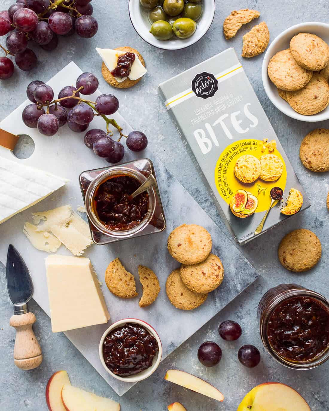 Flatlay of tomato, chilli and caraway jam with cheeses, grapes, apple and Arden's Lockerbie cheddar and caramelised onion chutney bites