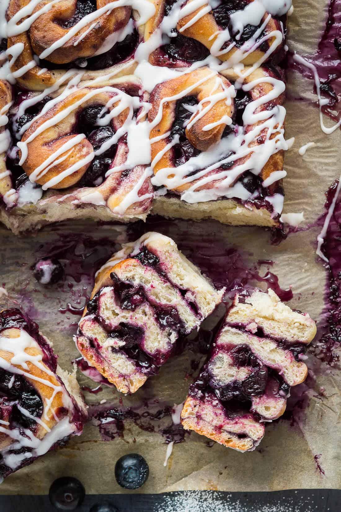 Vegan lemon blueberry sweet rolls filled with blueberry jam and fresh blueberries, topped with a lemon glaze.