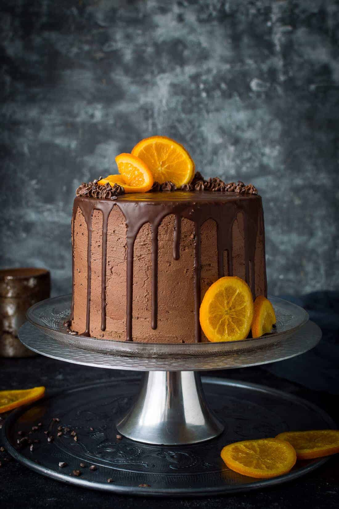 Vegan chocolate, orange and almond cake topped with chocolate drip and candied orange slices on a metal cake stand with a grey background