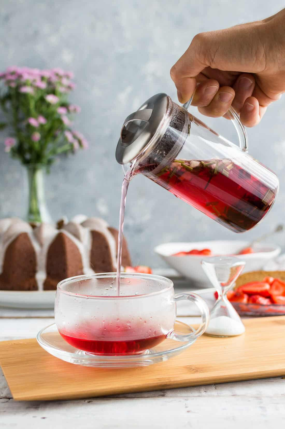 JING Green Apple and Hibiscus herbal tea being poured into a glass teacup