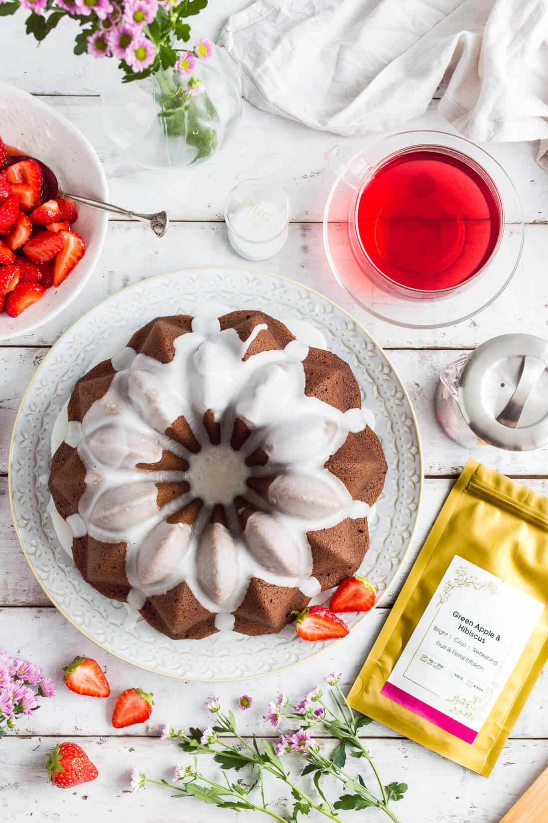 Vegan ginger bundt cake with lime glaze and macerated strawberries paired with JING Green Apple and Hibiscus herbal tea.
