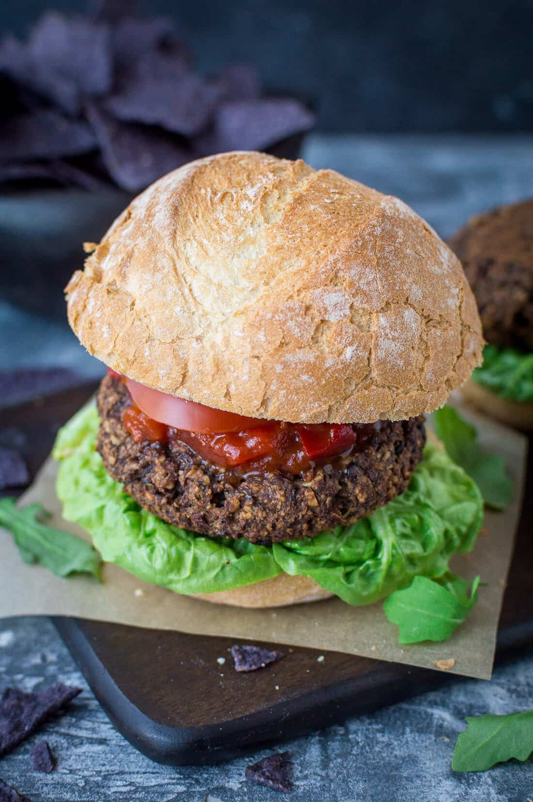 Vegan mushroom, lentil and walnut burger in a roll with lettuce and tomato salsa.