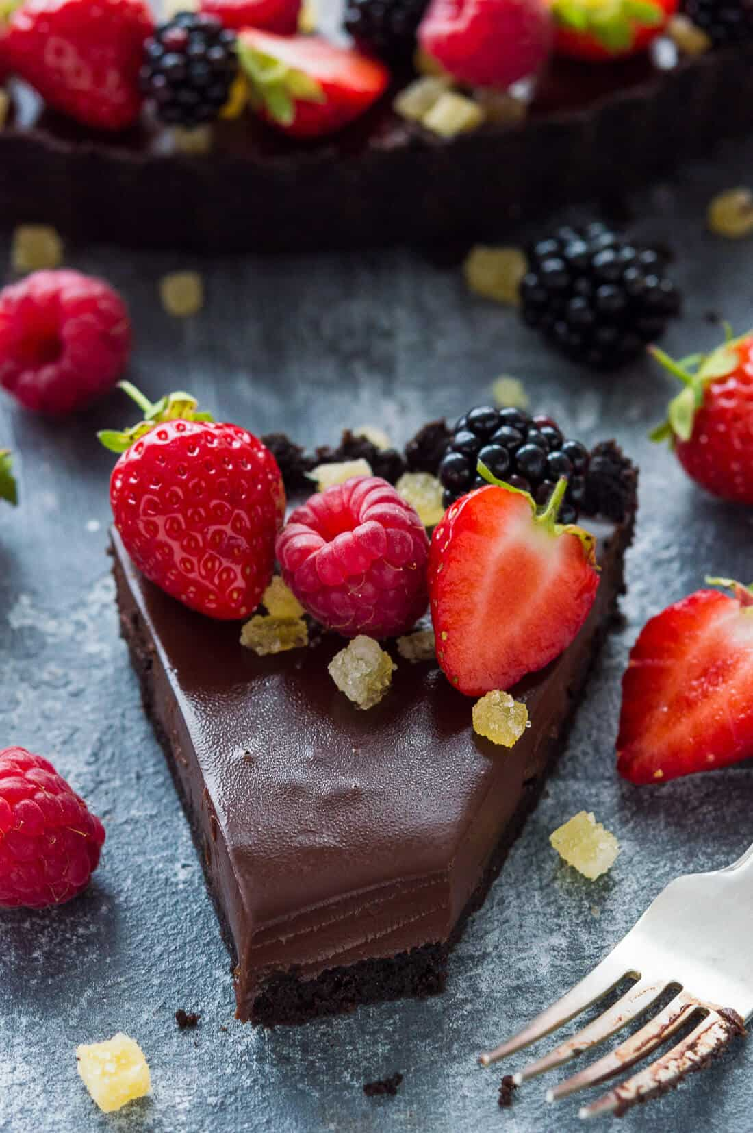 A slice of no-bake vegan chocolate tart with stem ginger - an Oreo biscuit base filled with coconut milk chocolate gananche and stem ginger.