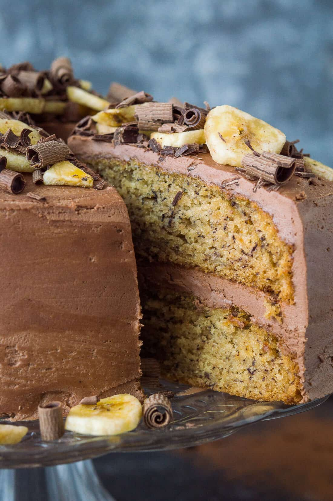 Close up of sliced vegan banana cake with chocolate peanut butter buttercream, banana chips and chocolate curls.