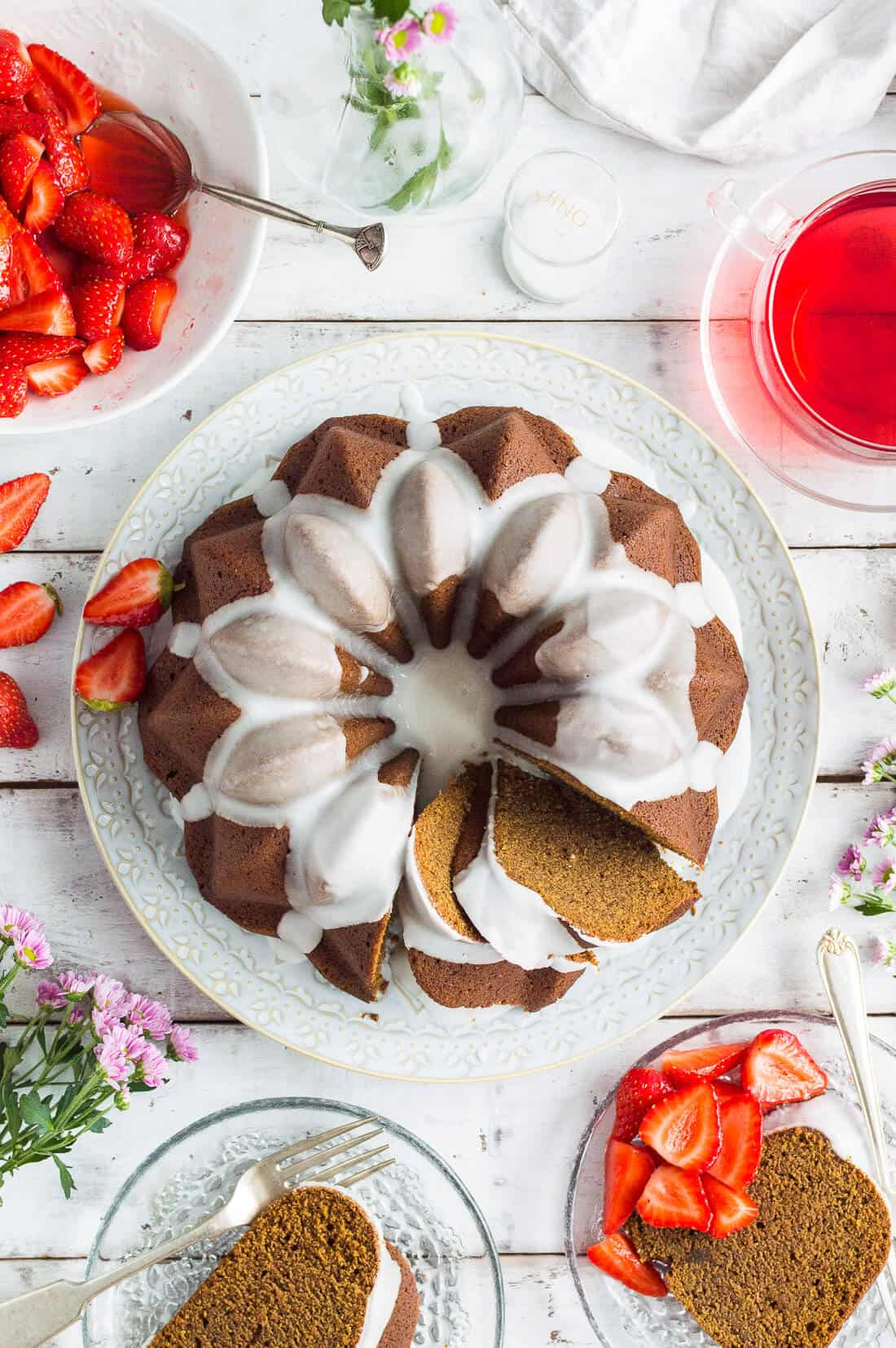 A top down shot of sliced vegan ginger bundt cake with lime glaze, macerated strawberries and green apple and hibiscus herbal tea on a white wooden background.