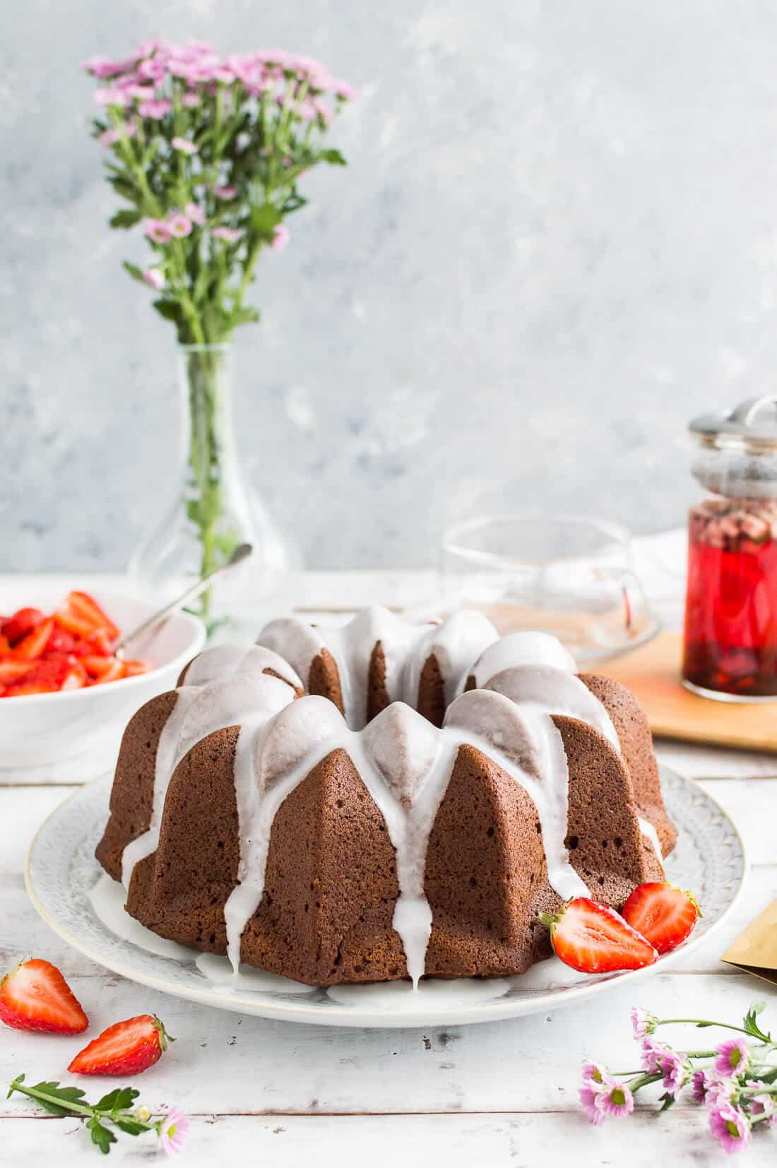 Vegan gingerbread bundt cake with a lime glaze and macerated strawberries served with tea