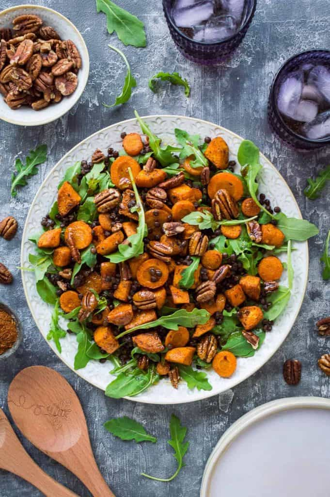 A plate of vegan roasted sweet potato, lentil and rocket salad with toasted pecans and pomegranate molasses dressing
