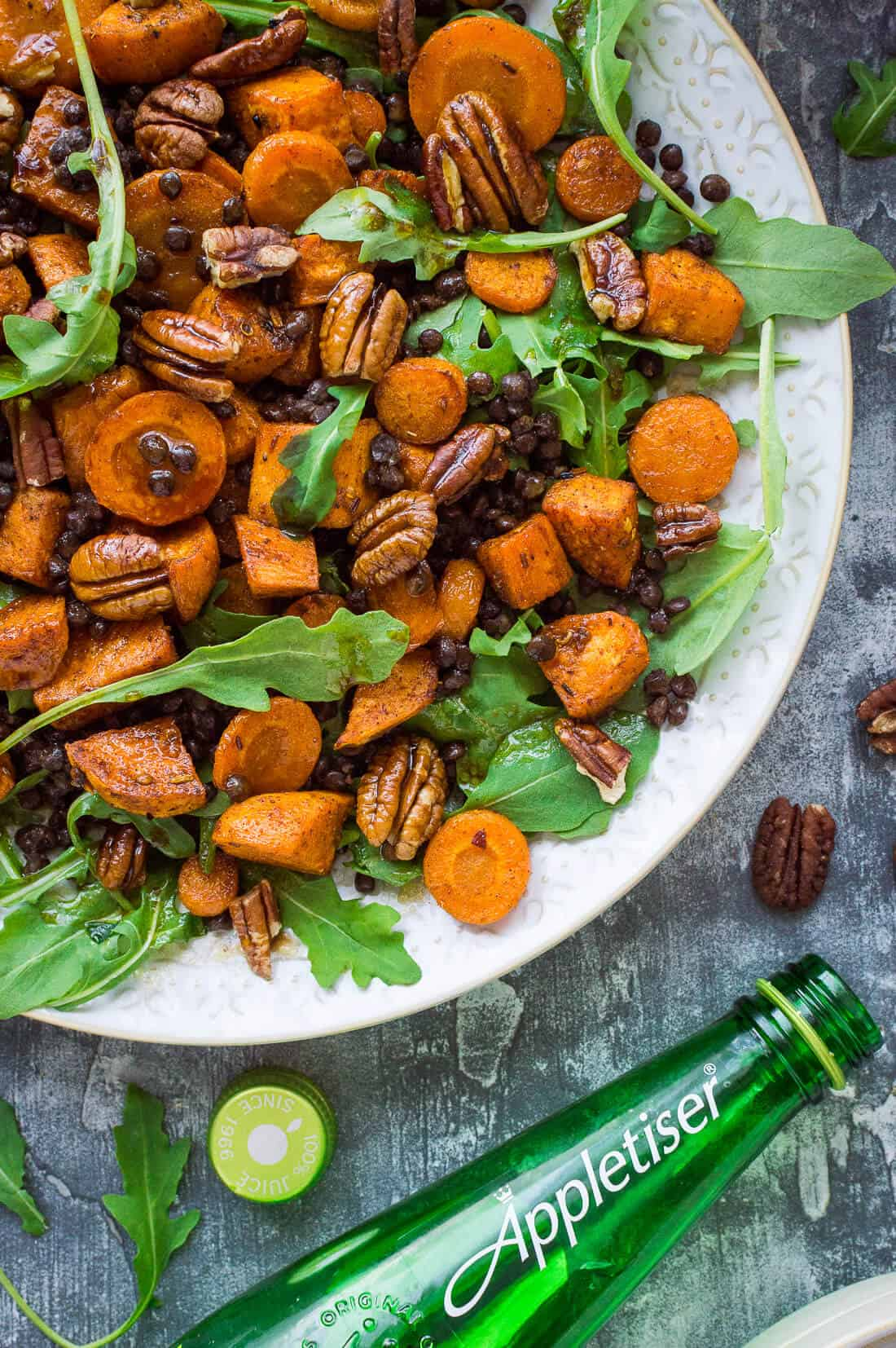 A close up of a plate of roasted sweet potato, lentil and rocket salad with a bottle of Appletiser