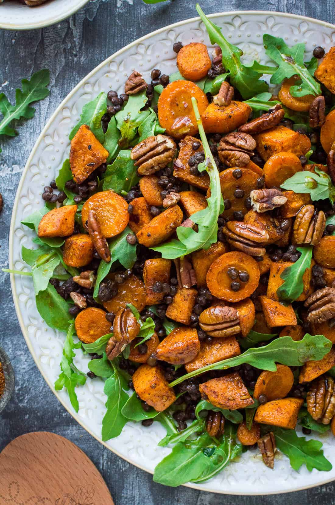 Roasted sweet potato, lentil and rocket salad – this hearty salad is filled with Ras el Hanout spiced roasted sweet potato and carrot, puy lentils, rocket  (arugula) and toasted pecans. #vegan #salad #healthy