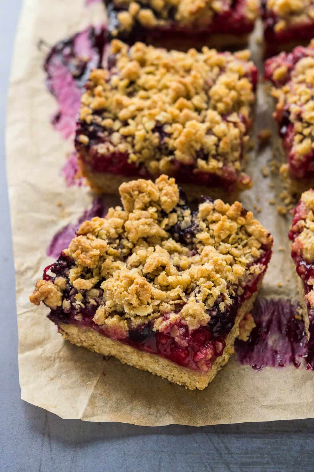 Angled shot of vegan berry oat crumble bars on baking parchment