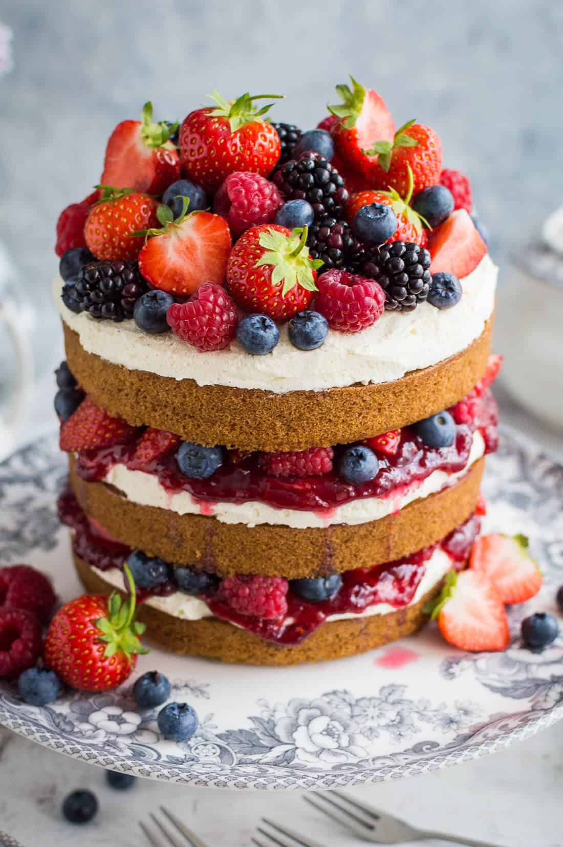 Close up of vegan vanilla cake with vanilla buttercream, raspberry jam and berries