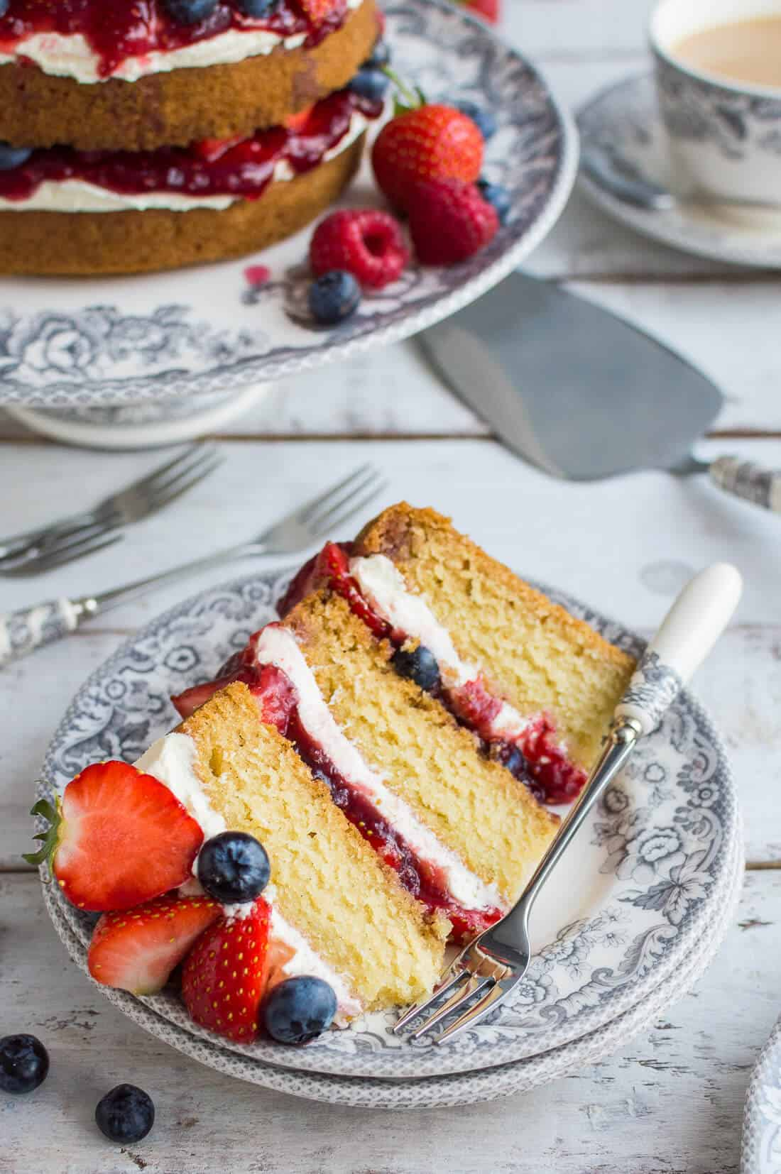 A slice of vegan vanilla cake with berries and jam on a grey Spode Delamere Rural plate with pastry fork.