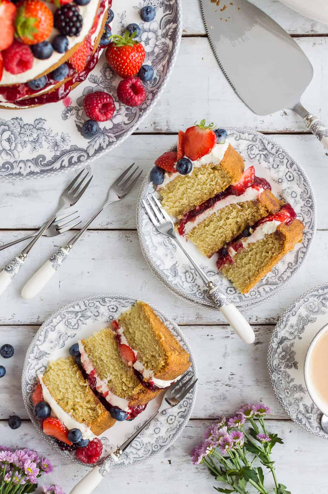 Slices of vegan vanilla cake with vanilla buttercream, berries and jam on grey plates on a white wooden background.