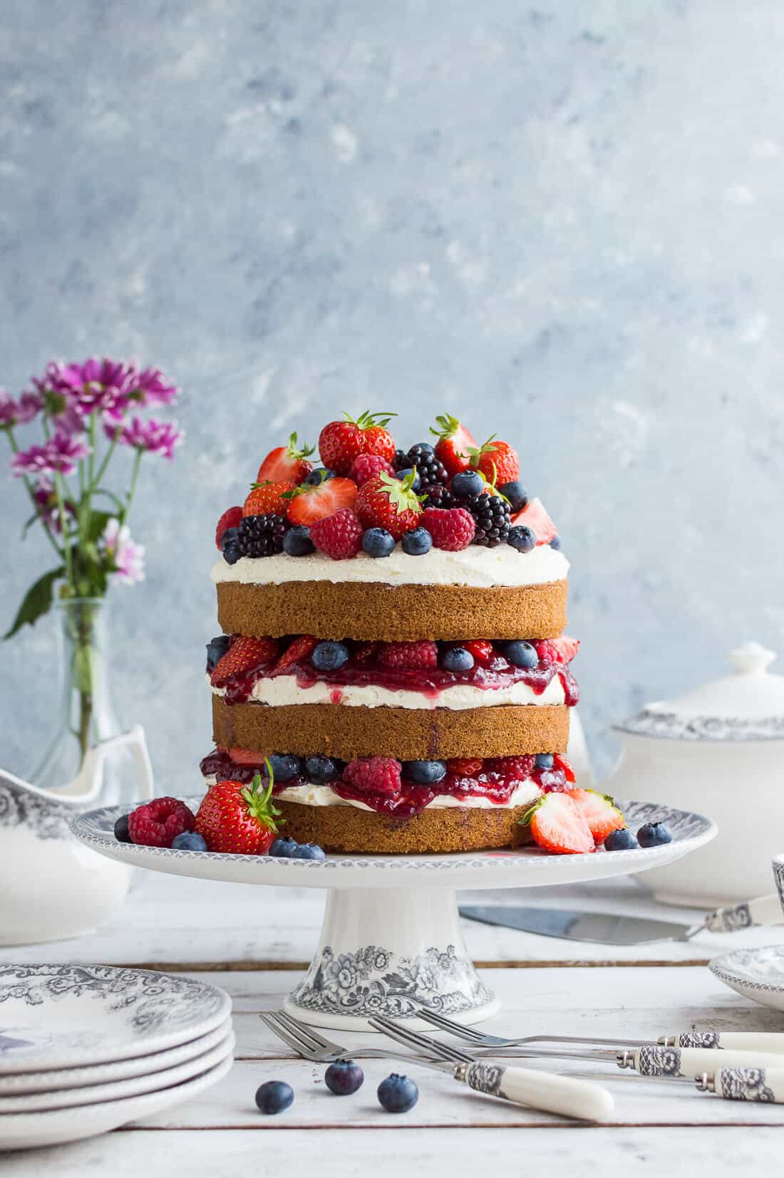 Vegan vanilla cake with berries and jam on a grey and white cake stand with crockery and flowers in the background.