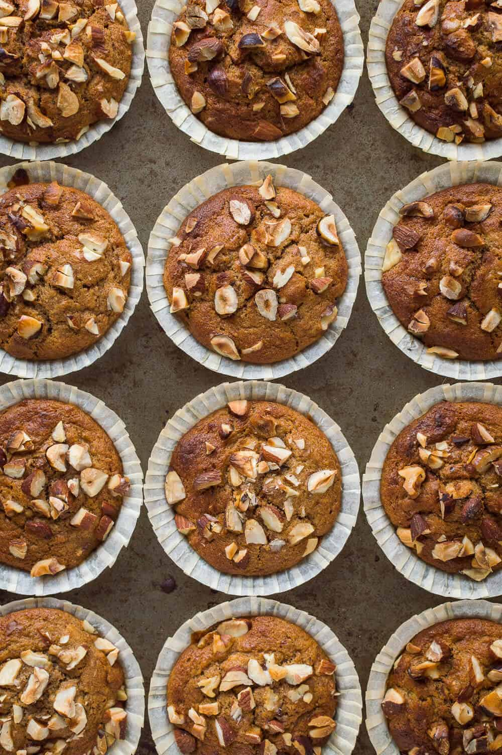 Top down photo of a tray of vegan banana nut muffins.