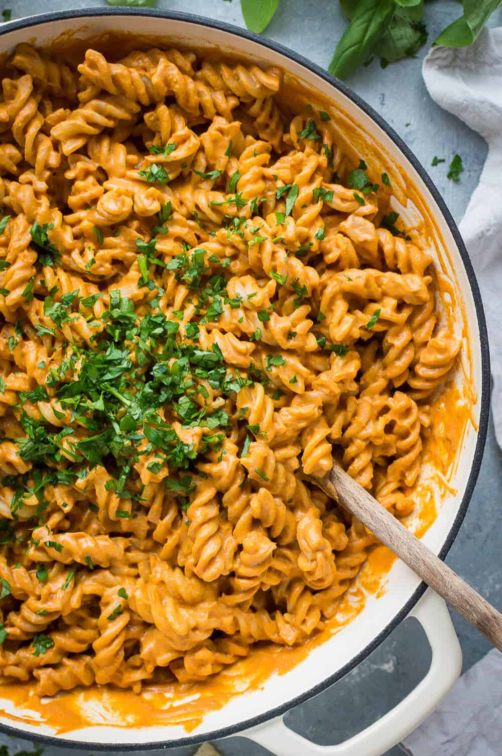 Close up of a pan of vegan creamy roasted red pepper tomato pasta topped with chopped herbs.