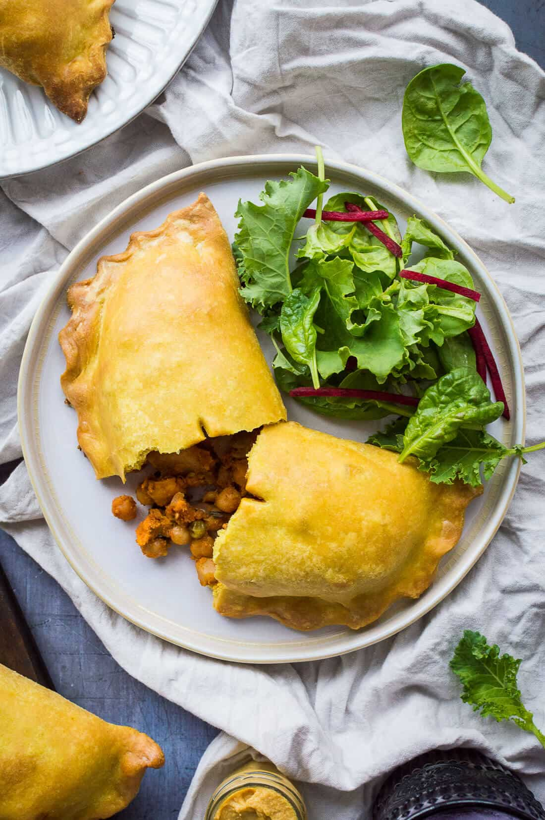 A vegan curried vegetable and chickpea pasty on a white plate with salad