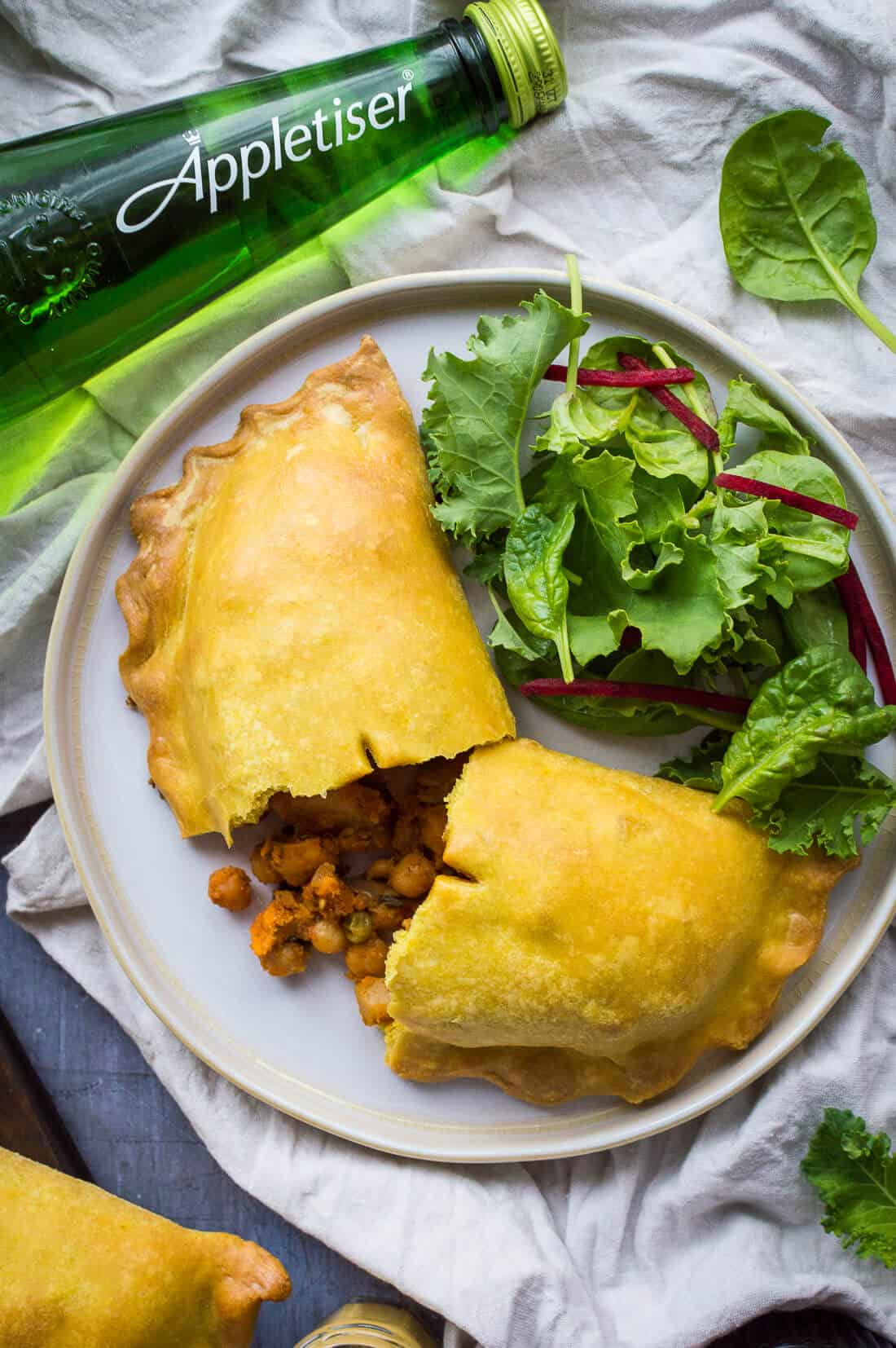 Close up of a vegan curried vegetable pasty with salad and a bottle of Appletiser