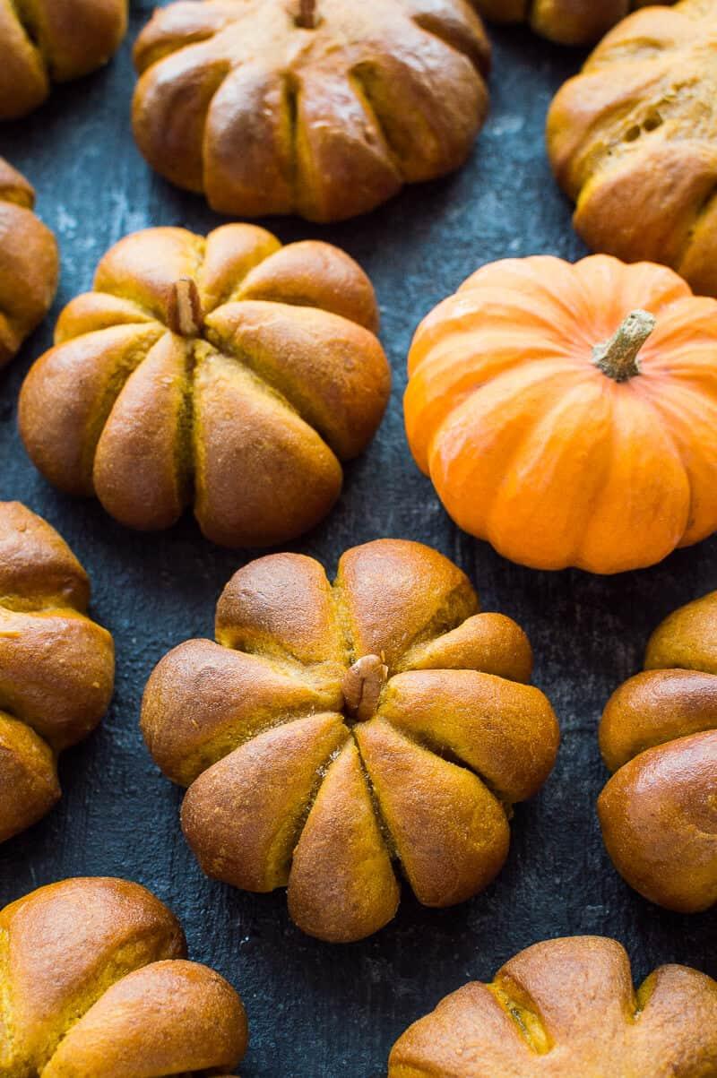 Pumpkin flavoured dinner rolls shaped like little pumpkins on a balck background with mini fresh pumpkins.