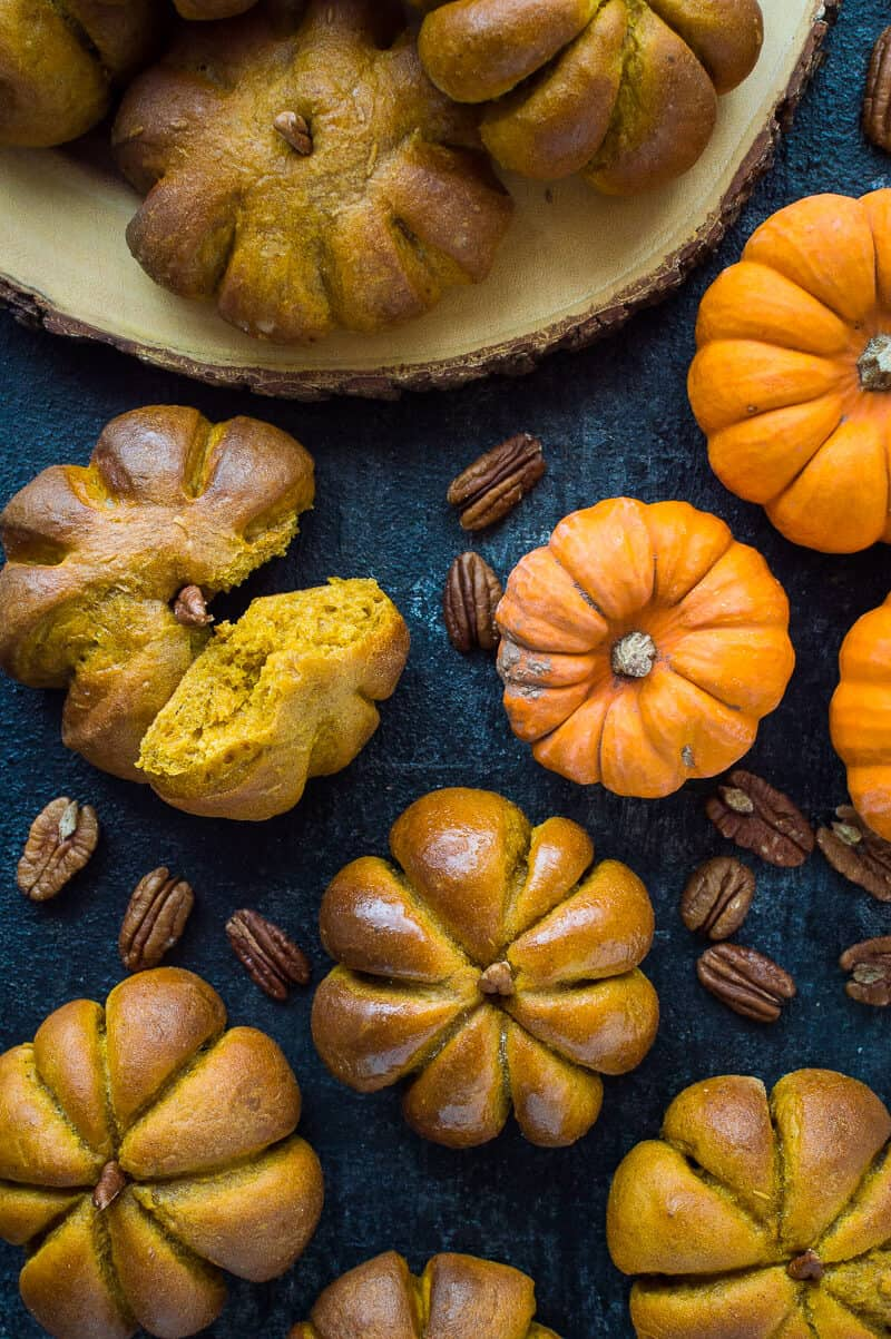 Pumpkin dinner rolls on a black background and wooden board with pecans and mini pumpkins.