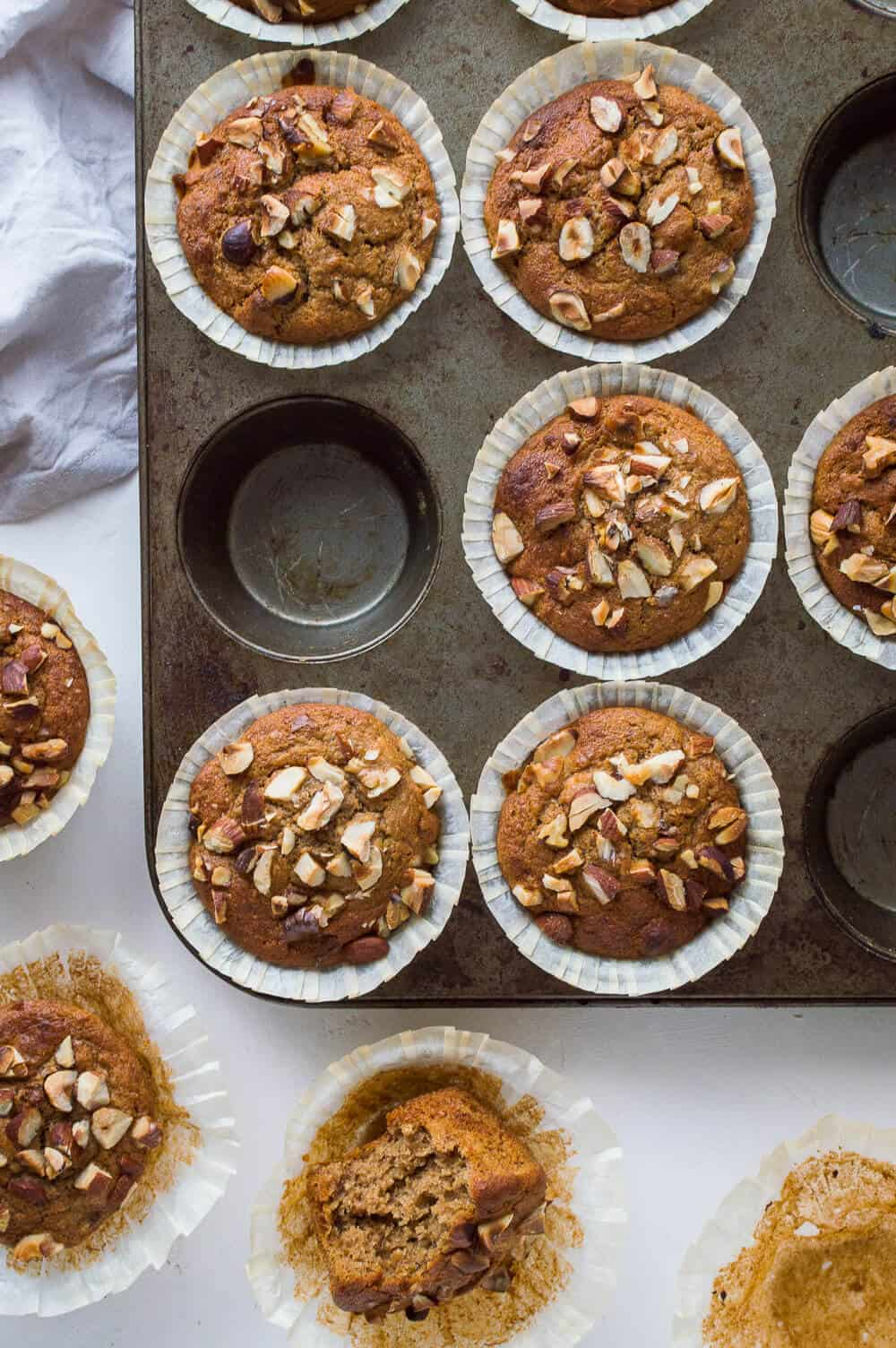 A tray of vegan banana nut muffins on a white background.
