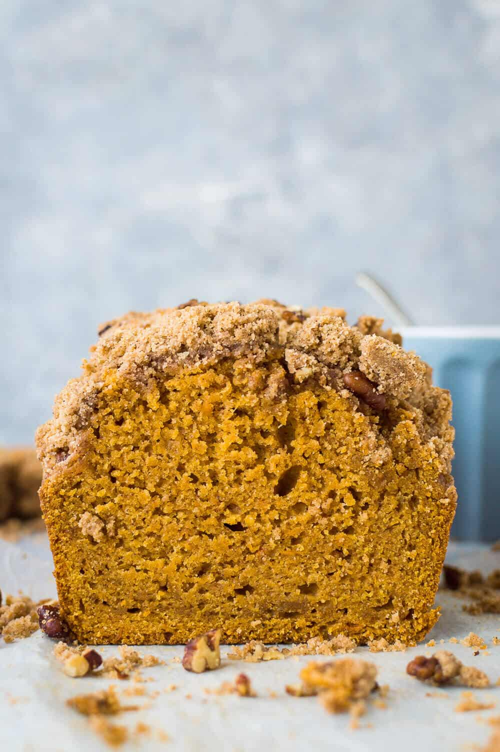 Face on photo of vegan sweet potato loaf with pecan crumble topping on a grey background.